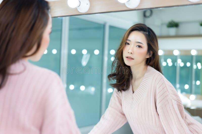 Ritratto di signora asiatica caucasica ispirata che indossa rosa tricottato del maglione con bello trucco che esamina macchina fo immagine stock libera da diritti