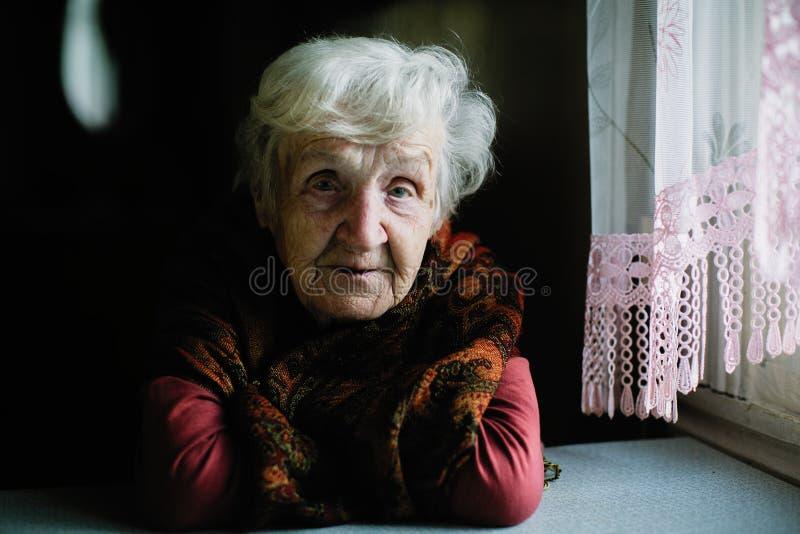 Ritratto di signora sola anziana che si siede nella casa immagini stock