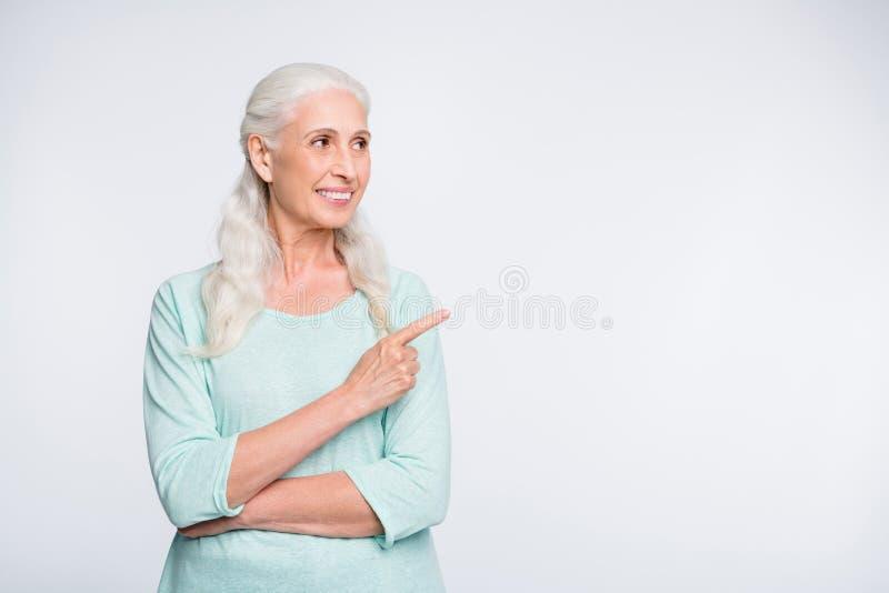 Ritratto di signora sveglia che mostra gli annunci che sembrano il pullover d'uso dell'alzavola isolato sopra fondo bianco fotografie stock libere da diritti