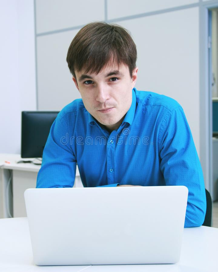 Ritratto di Smilling di un uomo davanti ad un computer portatile in ufficio immagini stock libere da diritti