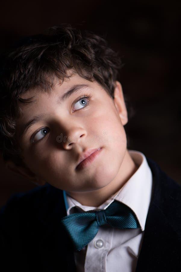 Ritratto di sogno del ragazzo giovane sveglio sui precedenti scuri fotografia stock
