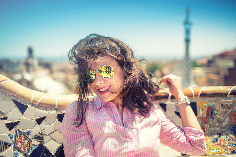 Ritratto di sorridere, ragazza castana splendida con gli occhiali da sole un giorno ventoso fotografia stock