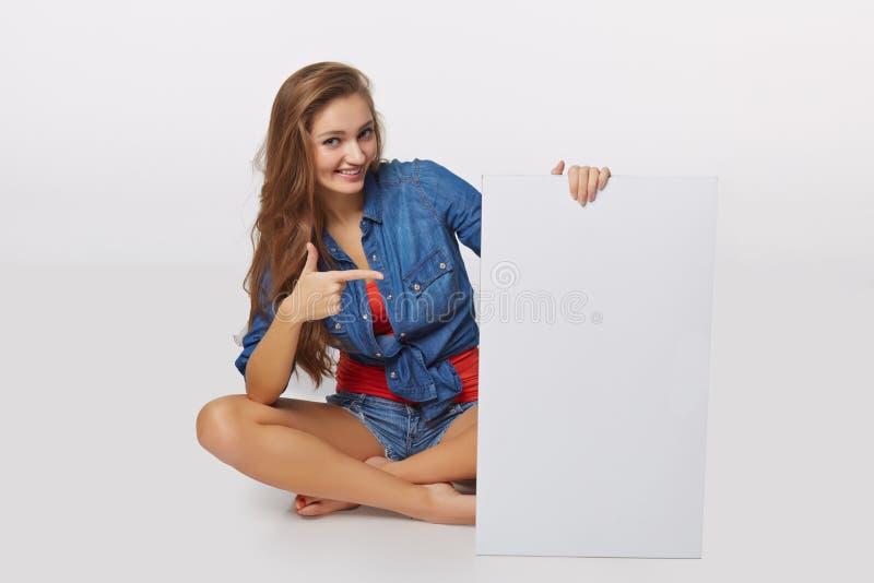 Ritratto di stile del denim della ragazza teenager sul pavimento che tiene bla bianco fotografie stock