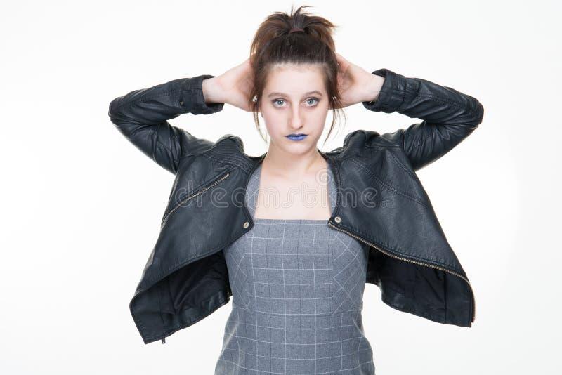 Ritratto di stile della roccia della ragazza in vestiti di cuoio che posano contro lo studio bianco fotografia stock
