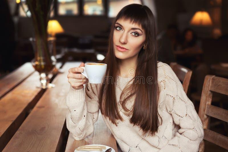 Ritratto di stile di vita del primo piano della giovane donna graziosa nel caffè bevente e nel sogno del maglione della lana Prim immagini stock libere da diritti