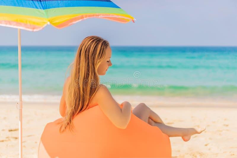Ritratto di stile di vita di estate della ragazza graziosa che si siede sul sofà gonfiabile arancio sulla spiaggia dell'isola tro immagini stock