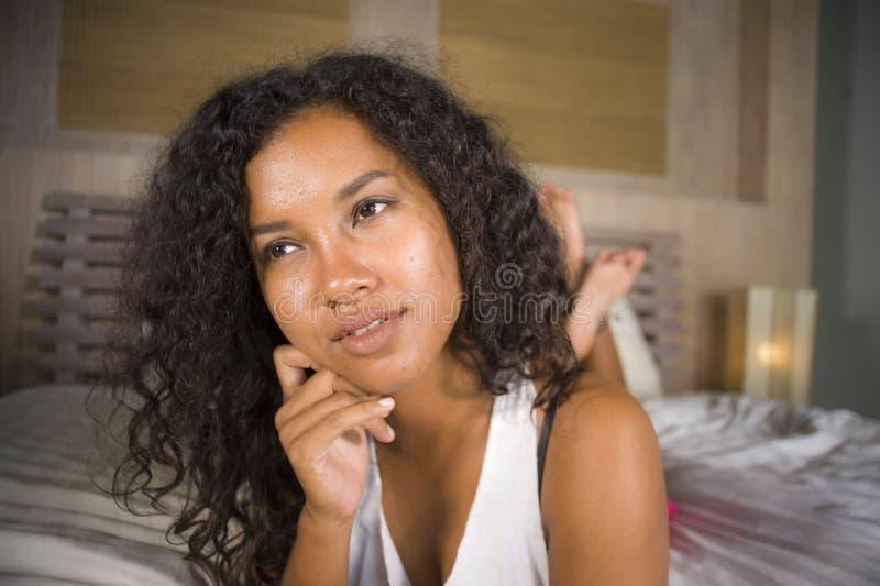 Ritratto di stile di vita di giovane donna americana dell'africano nero felice e splendido che posa a casa menzogne sexy ed alleg fotografia stock