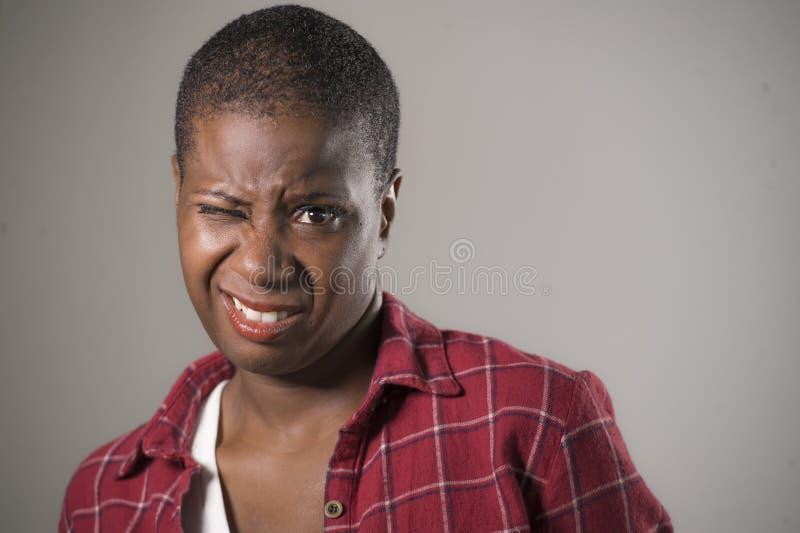 Ritratto di stile di vita se giovane donna afroamericana infelice e graziosa nell'espressione del fronte di repulsione e di dispr fotografia stock