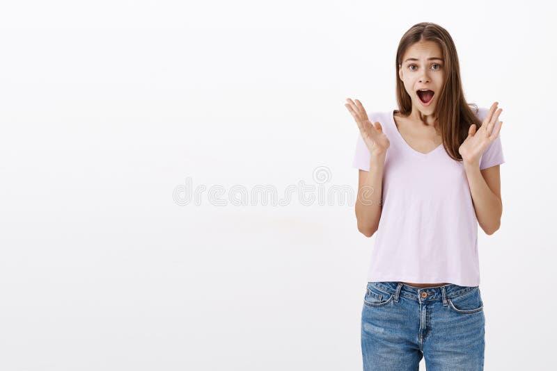Ritratto di studentessa europea abbastanza giovane emotiva in maglietta casuale che urla dalla stupefazione e dalla gioia che si  fotografia stock