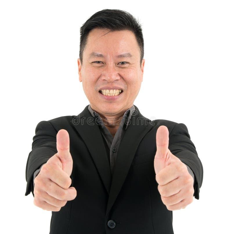Ritratto di successo attuale dell'uomo d'affari sicuro mostrando due pollici, isolato su fondo bianco fotografia stock