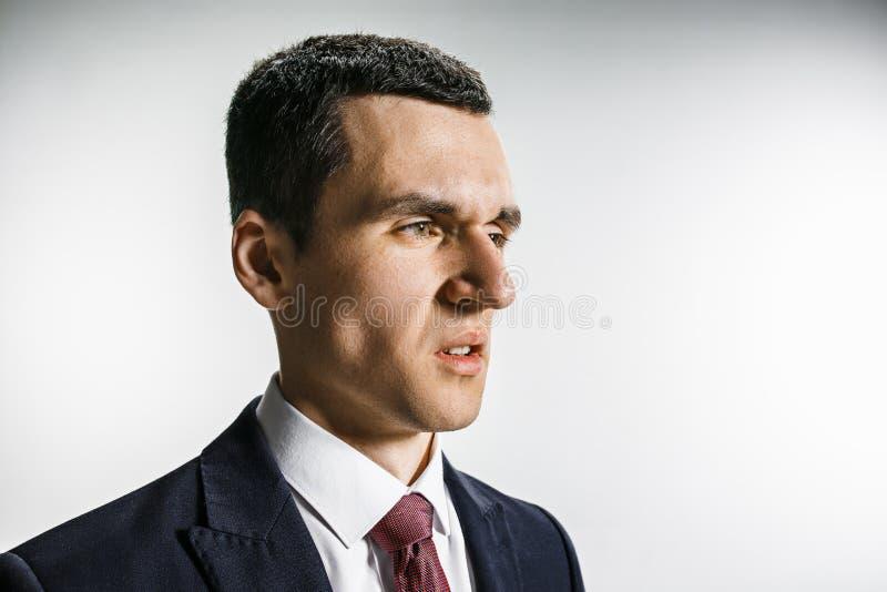 Ritratto di tre quarti di un uomo d'affari con il fronte di repulsione Professionista sicuro con lo sguardo di piercing nella pri immagini stock