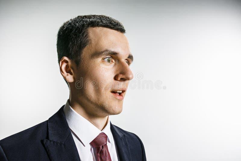 Ritratto di tre quarti di un uomo d'affari con il fronte sorpreso e sorridente Professionista sicuro con lo sguardo di piercing d immagini stock