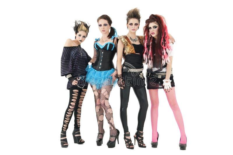 Ritratto di tutta la banda rock femminile che posa insieme sopra il fondo bianco immagini stock