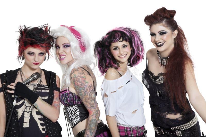 Ritratto di tutta la banda rock femminile con il microfono sopra fondo bianco fotografia stock