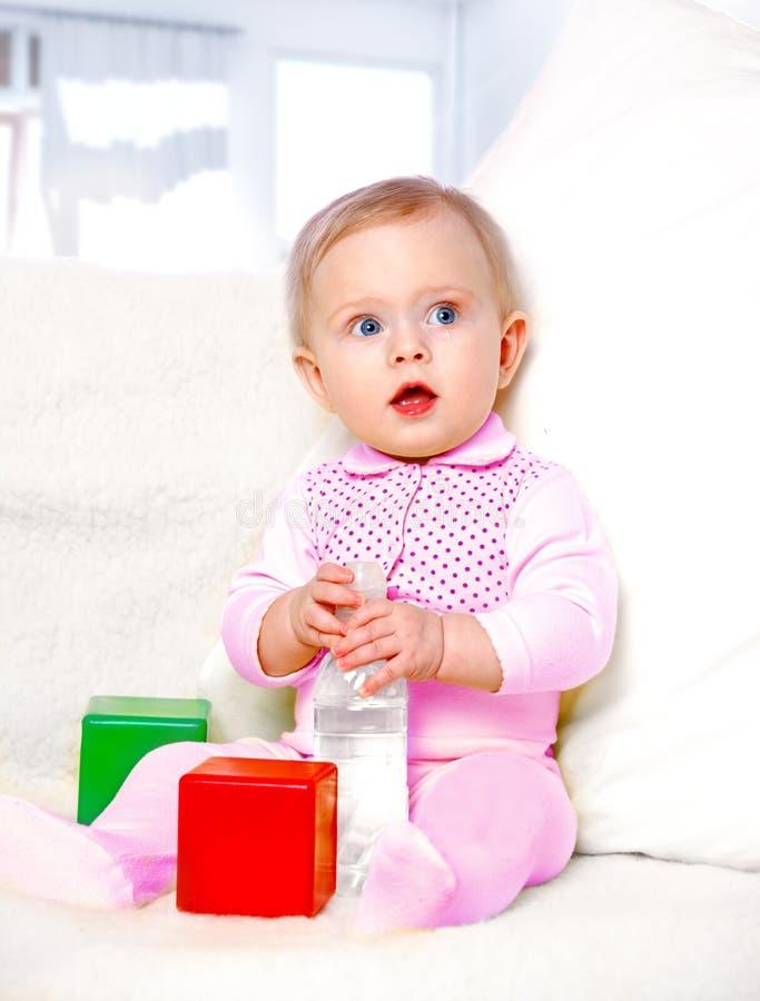 Ritratto di un'acqua potabile della bambina allegra da una bottiglia fotografia stock libera da diritti