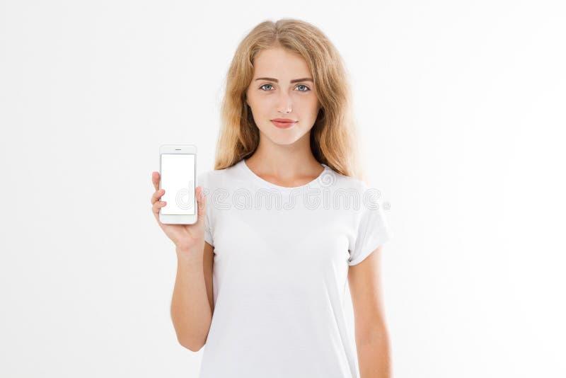 Ritratto di un adolescente di buon umore felice vestito in maglietta bianca che tiene il telefono cellulare dello schermo in bian fotografia stock libera da diritti
