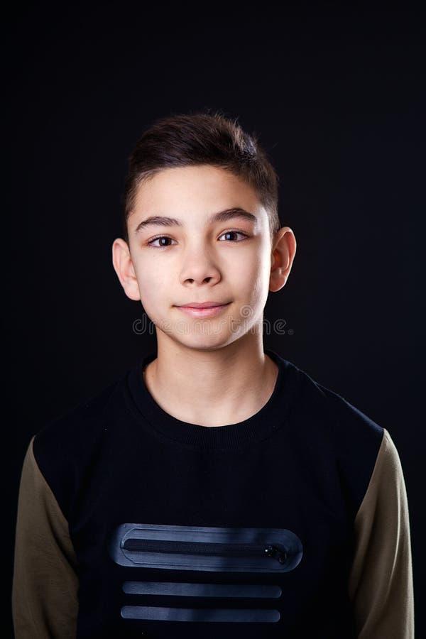 Ritratto di un adolescente Il tipo nella maglietta nera su un fondo nero ? isolato immagini stock libere da diritti