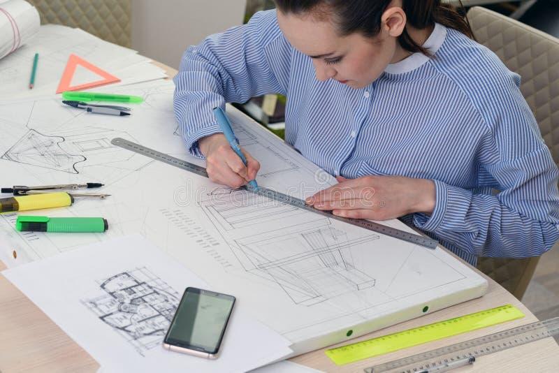 Ritratto di un architetto della donna sul lavoro su un progetto di progettazione della costruzione, sulla carta della tavola, rig fotografia stock libera da diritti