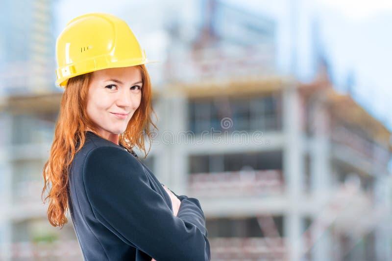 ritratto di un architetto femminile in un casco giallo ad una costruzione fotografia stock libera da diritti