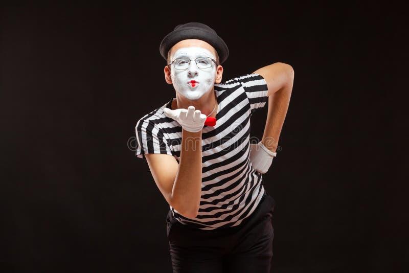 Ritratto di un artista mime, isolato su fondo nero L'uomo si è piegato per far saltare un bacio fotografia stock