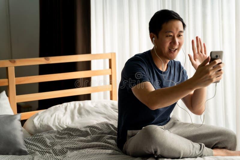 Ritratto di un asiatico di 30 anni felice in abbigliamento casuale che fa videochiamate con smartphone a casa E'... fotografie stock