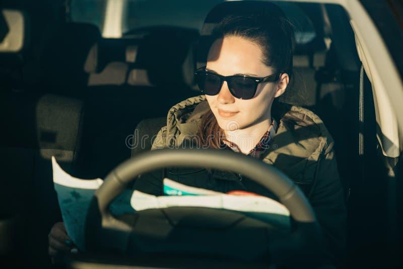 Ritratto di un autista del turista o della ragazza della giovane donna dentro un'automobile che esamina la mappa per un viaggio s immagini stock
