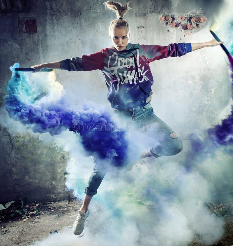 Ritratto di un ballerino di salto che tiene i chiarori variopinti fotografia stock