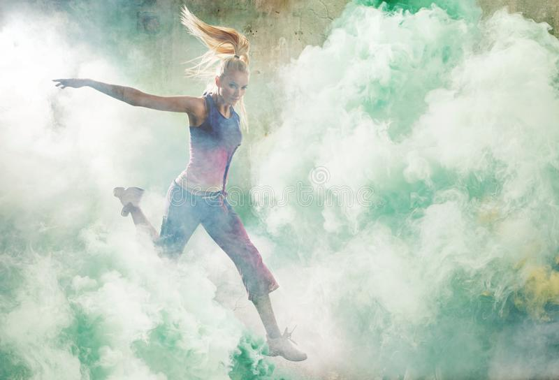 Ritratto di un ballerino di salto che tiene i chiarori variopinti fotografie stock libere da diritti