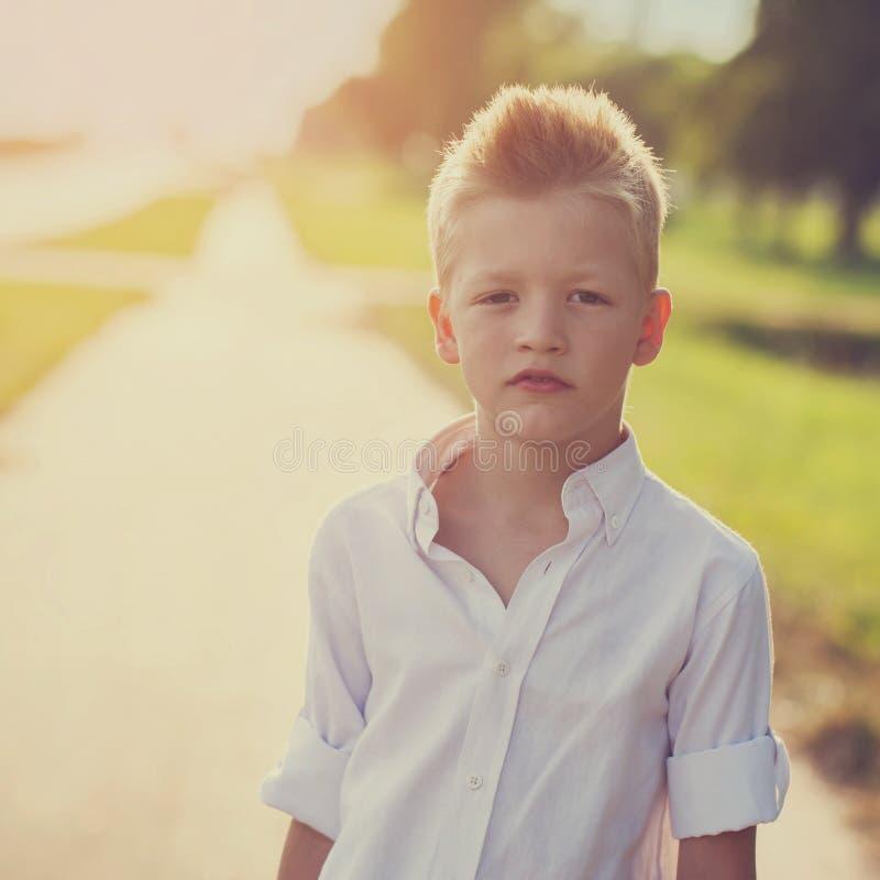 Ritratto di un bambino piacevole sulla strada nel soleggiato immagine stock libera da diritti