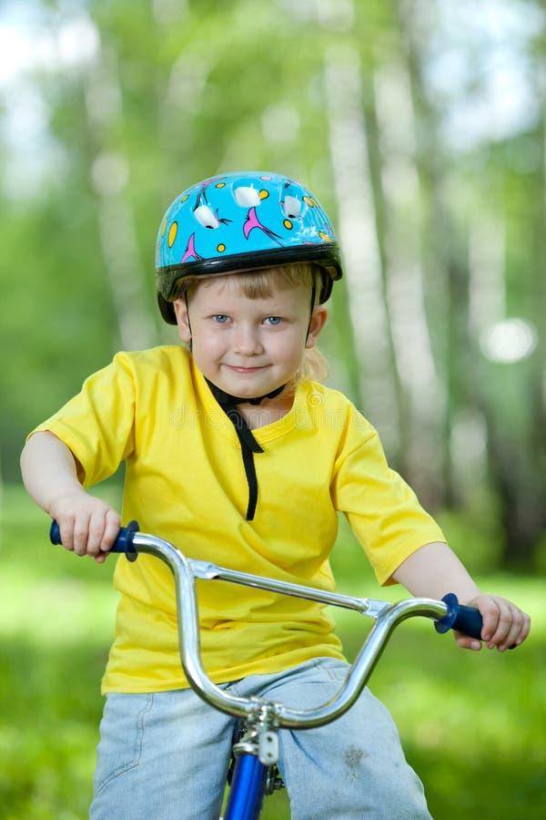 Ritratto di un bambino sveglio sulla bicicletta all'aperto immagine stock libera da diritti