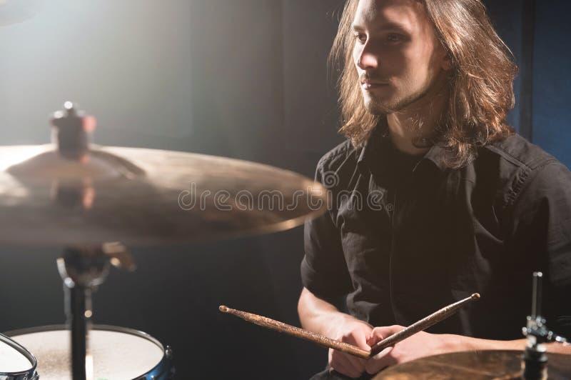 Ritratto di un batterista dai capelli lunghi con i bastoncini in sue mani che si siedono dietro un insieme del tamburo Esaminando fotografia stock libera da diritti
