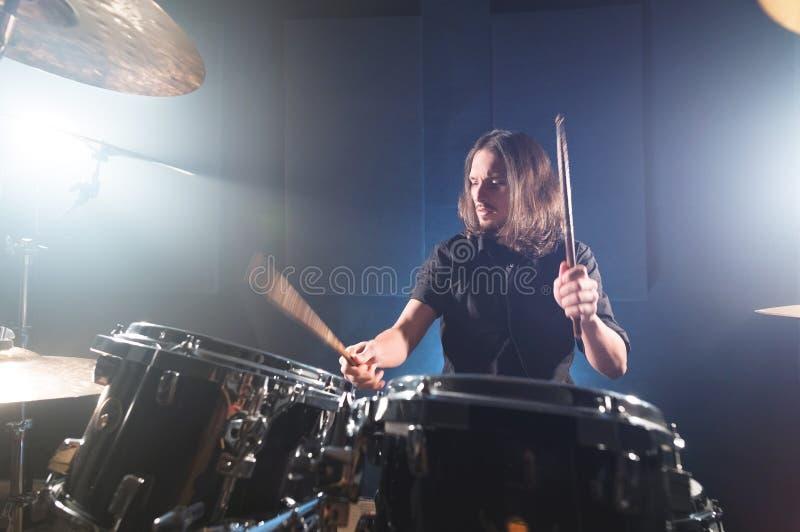 Ritratto di un batterista dai capelli lunghi con i bastoncini in sue mani che si siedono dietro un insieme del tamburo Esaminando immagini stock libere da diritti
