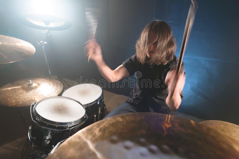 Ritratto di un batterista dai capelli lunghi con i bastoncini in sue mani che si siedono dietro un insieme del tamburo Esaminando fotografie stock