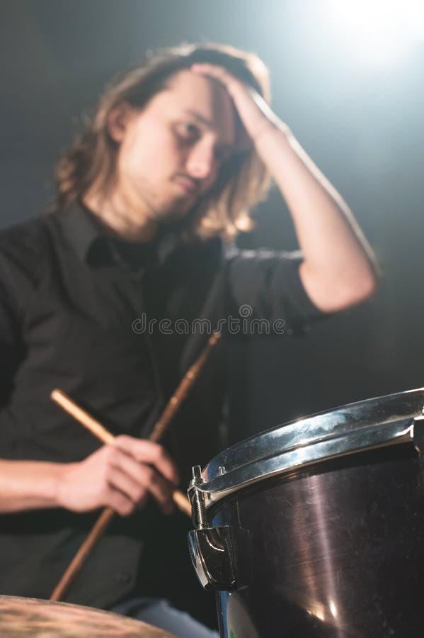 Ritratto di un batterista dai capelli lunghi in defocus con i bastoncini in sue mani che si siedono dietro un insieme del tamburo immagini stock libere da diritti