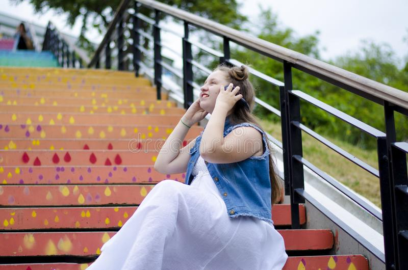 Ritratto di un bello, ragazza che si siede sulle scale ed ascolta musica sulle cuffie, nella via, di estate fotografia stock