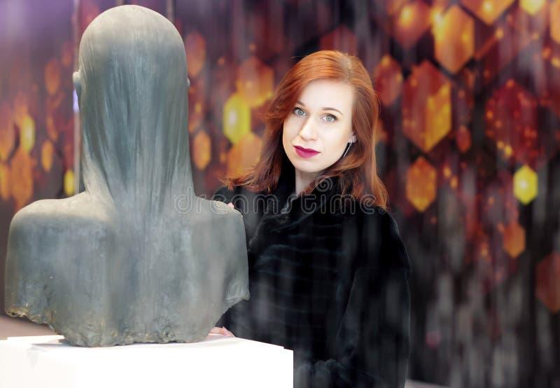 Ritratto di un bello, ragazza con un bello, trucco naturale e un rossetto rosso, i capelli rossi ed i vestiti neri stanti dietro immagini stock libere da diritti