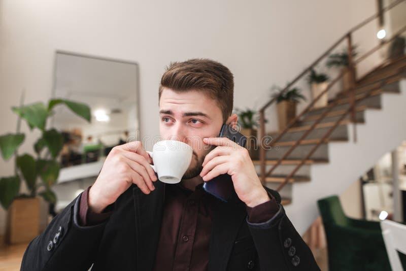 Ritratto di un caffè bevente dell'uomo occupato da una tazza e di conversazione sul telefono in un caffè accogliente immagine stock
