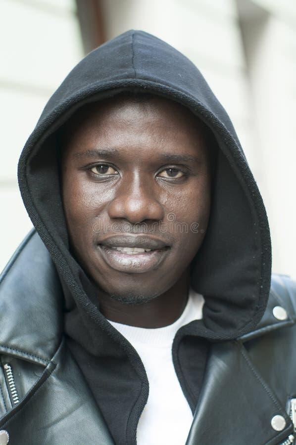 Ritratto di un cappuccio d'uso del giovane uomo di colore fotografia stock libera da diritti
