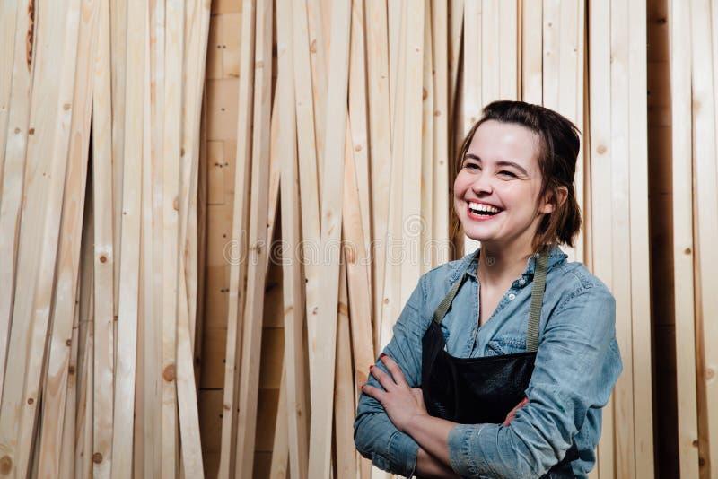 Ritratto di un carpentiere della femmina adulta in un grembiule Contro lo sfondo delle stecche di legno immagini stock