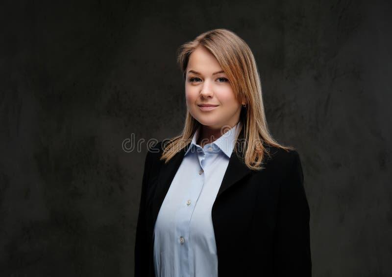 Ritratto di un convenzionale biondo sorridente della donna di affari vestito Isolato su fondo strutturato scuro fotografia stock libera da diritti