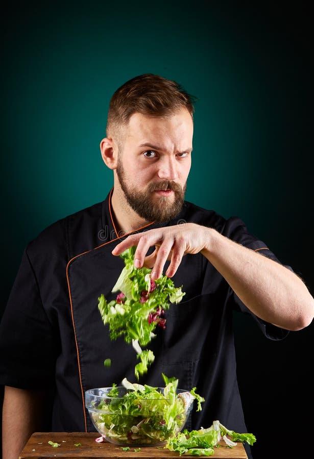 Ritratto di un cuoco maschio bello del cuoco unico che produce insalata saporita su un fondo vago dell'acquamarina immagine stock