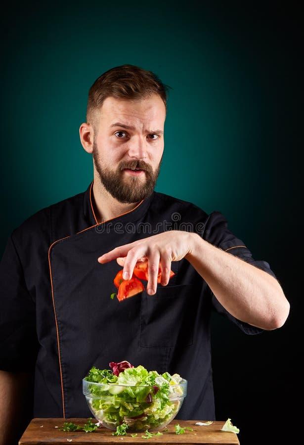 Ritratto di un cuoco maschio bello del cuoco unico che produce insalata saporita su un fondo vago dell'acquamarina immagini stock libere da diritti