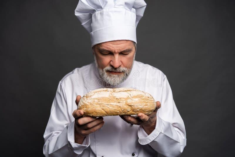 Ritratto di un cuoco maschio del cuoco unico che odora pane fresco contro il fondo nero immagine stock