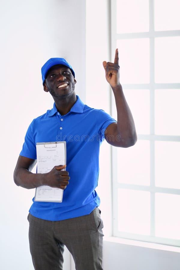 Ritratto di un deliverer felice bello con la cartella immagini stock libere da diritti