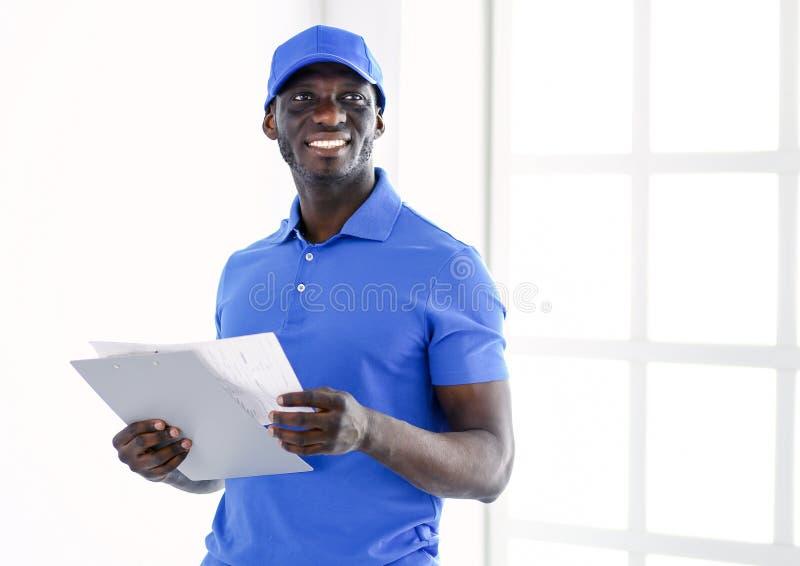 Ritratto di un deliverer felice bello con la cartella immagine stock libera da diritti