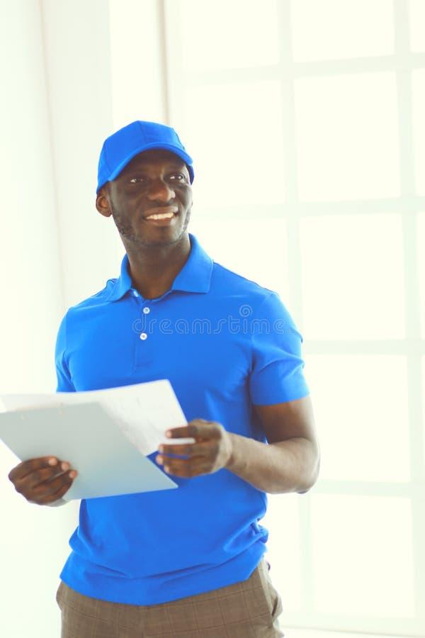Ritratto di un deliverer felice bello con la cartella immagini stock