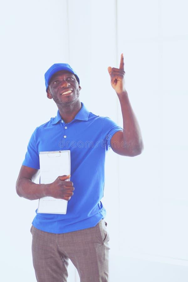 Ritratto di un deliverer felice bello con la cartella fotografia stock libera da diritti