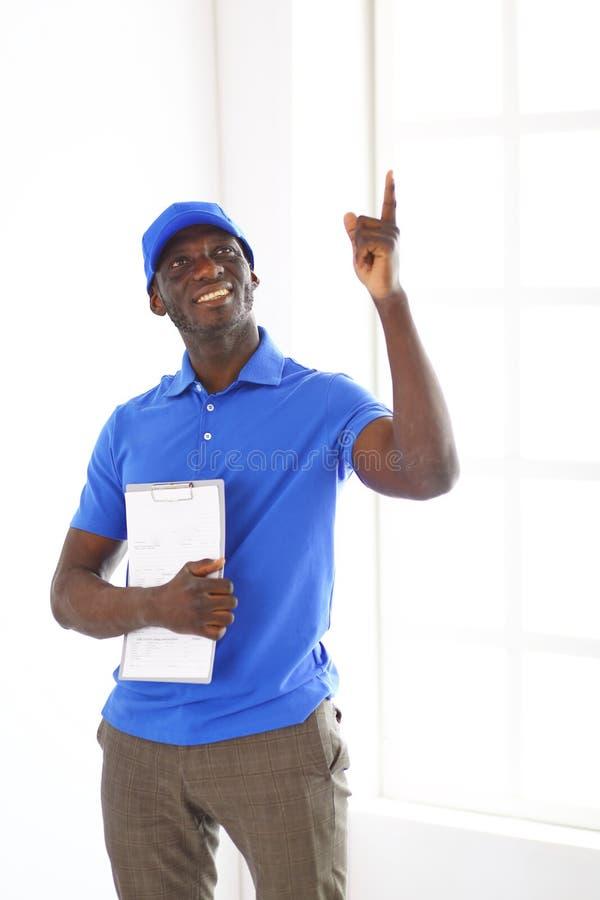 Ritratto di un deliverer felice bello con la cartella fotografie stock libere da diritti