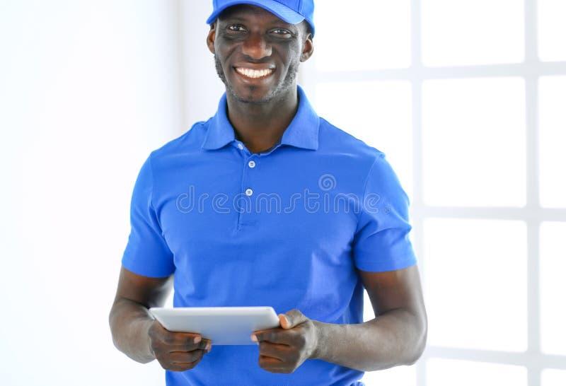 Ritratto di un deliverer felice bello con la cartella fotografie stock