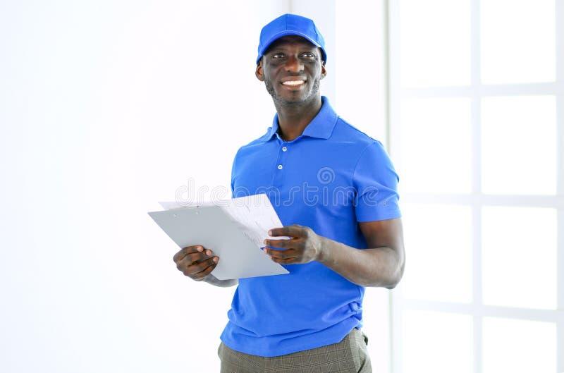 Ritratto di un deliverer felice bello con la cartella immagine stock